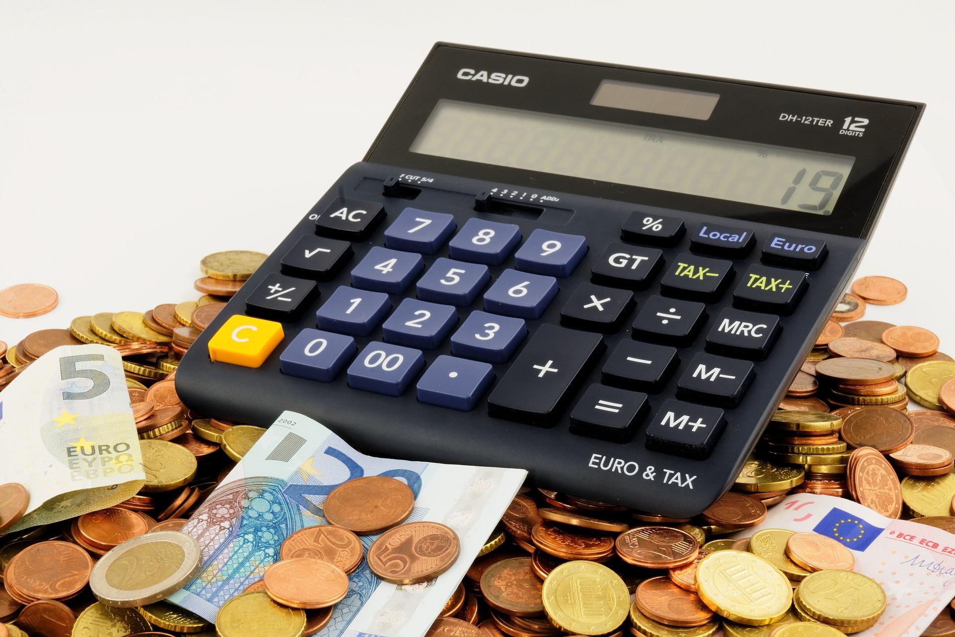 EIn Taschenrechner und einzelne Euro - Geldscheine auf Münzen