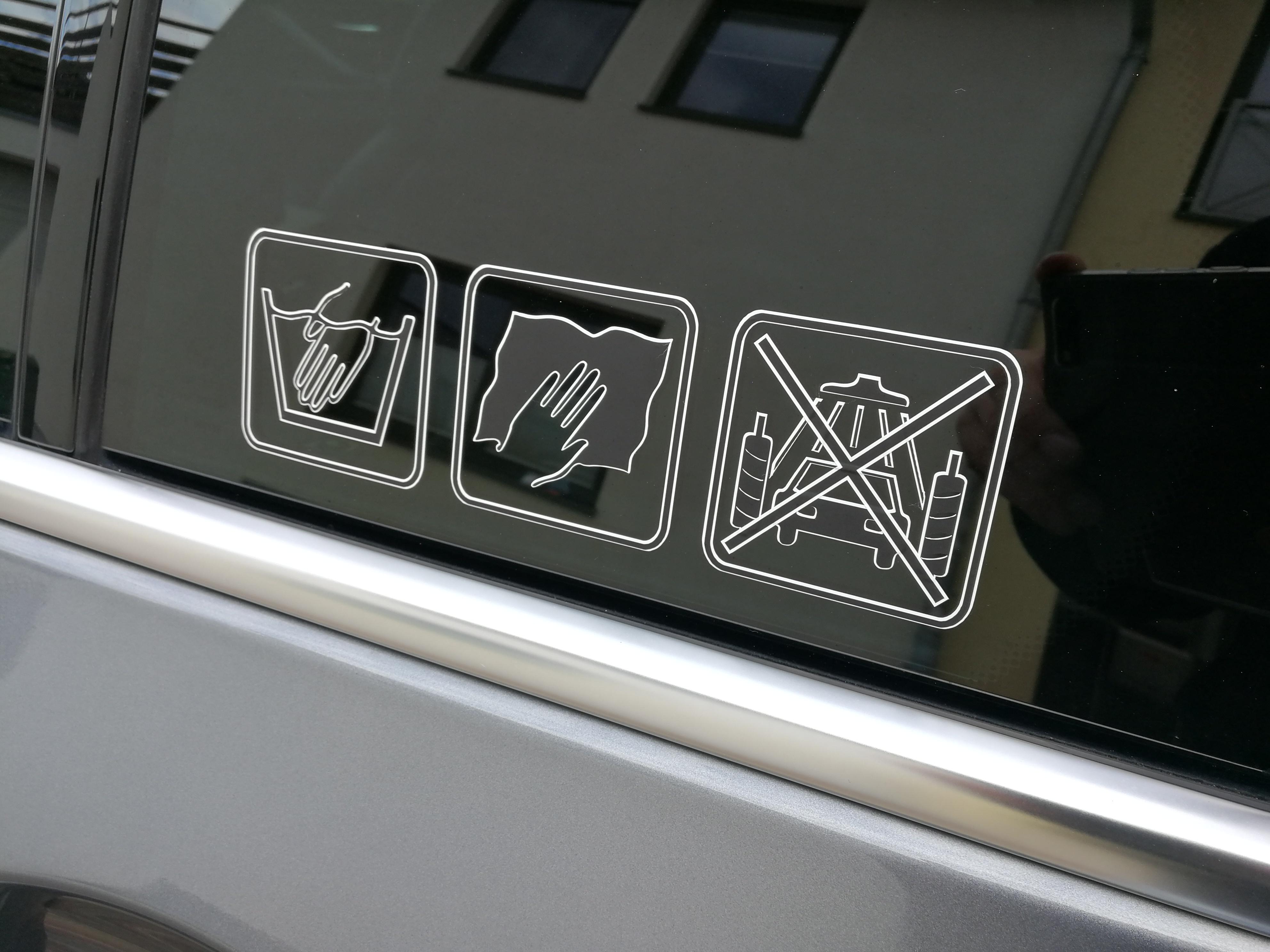 Dreiecksfenster eines BMW F11 530d mit einem hand wash only Aufkleber